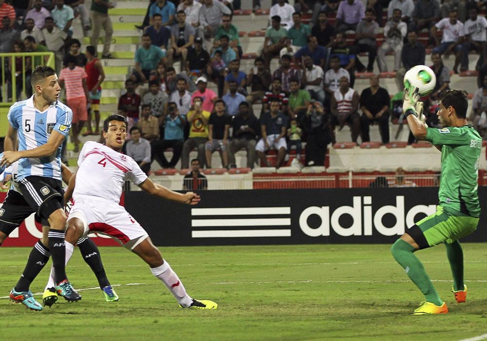 El jugador argentino Germán Ferreyra (i) marca el gol inaugural ante el jugador tunecino Marouane Sahraoui (c) y el guardamenta tunecino, Sabri Ben. EFE
