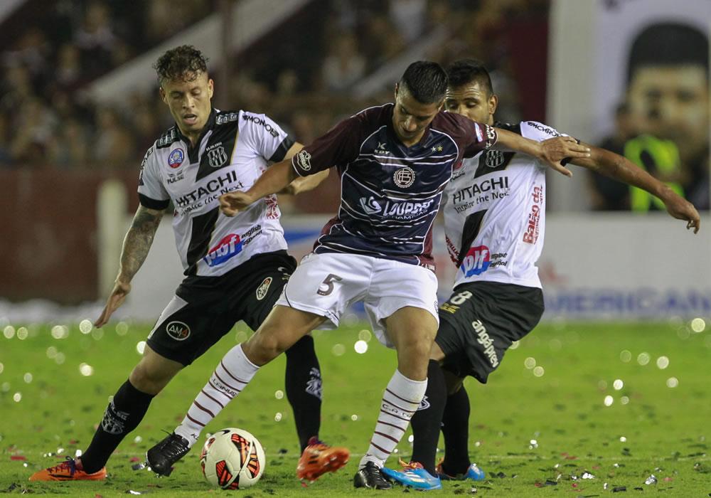El jugador de Lanús Diego González (c) es marcado por Cesar Ponte (d) y Fernando Bob (i), de Ponte Preta. Foto: EFE
