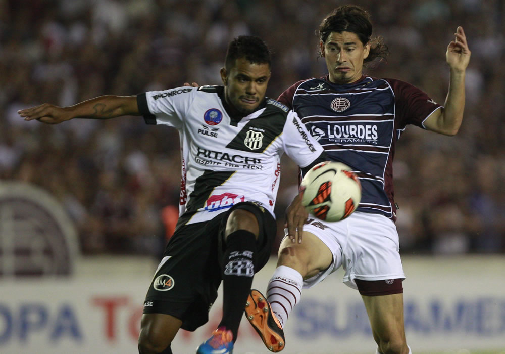 El jugador de Ponte Preta Fernando Bob disputa el balón con Ismael Blanco (d), de Lanús. Foto: EFE