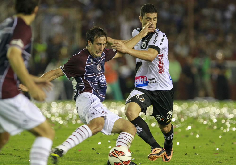 El jugador de Lanús Carlos Izquierdo (c) es marcado por Leonardo (d), de Ponte Preta. Foto: EFE