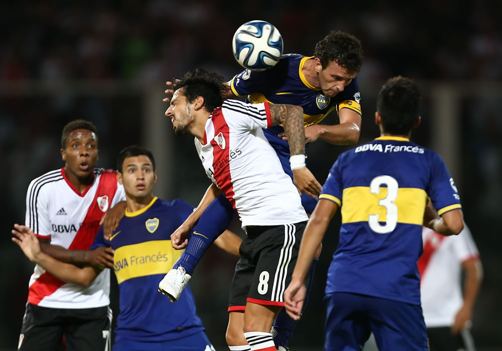 El jugador de Boca Juniors Pablo Ledezma (2-d) trata de cabecear el balón, durante un partido entre Boca Juniors y River Plate. EFE