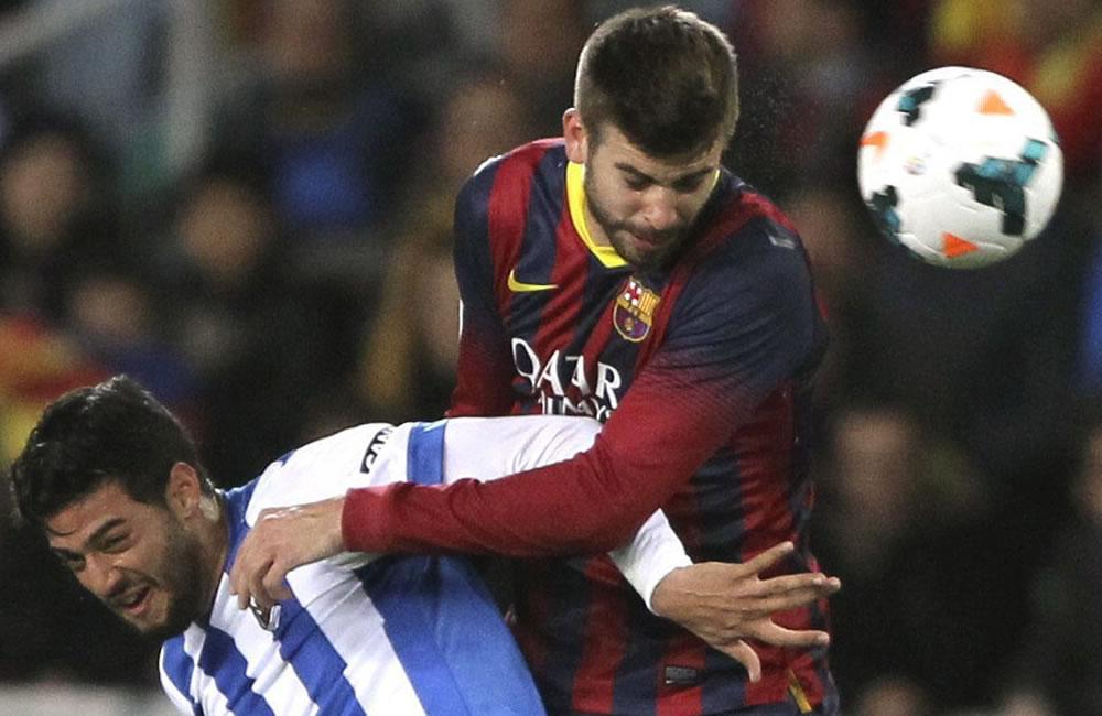 El defensa del FC Barcelona Gerard Piqué (d) cabecea un balón ante el mexicano Carlos Vela, de la Real Sociedad. Foto: EFE