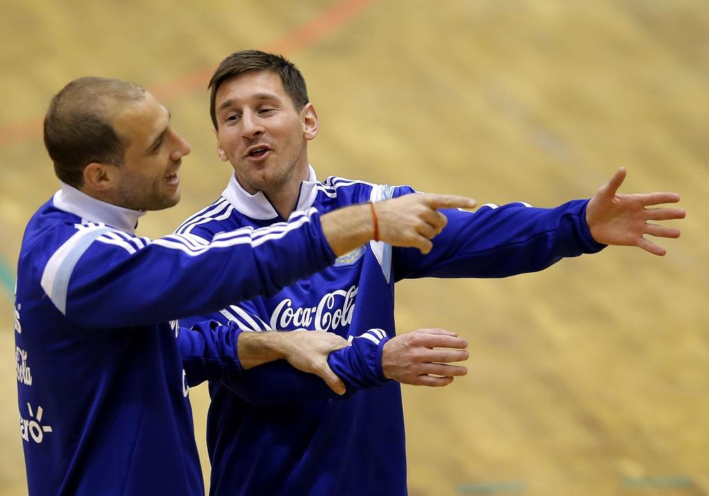 Los jugadores de la selección argentina de fútbol Lionel Messi (d) y Pablo Zabaleta (i) conversan durante el entrenamiento del equipo en el pabellón deportivo de Polivalenta de Bucarest. Foto: EFE