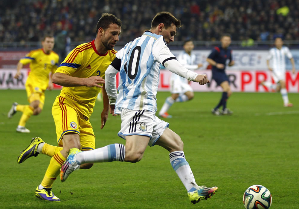 El delantero de la selección argentina, Leo Messi (d) lucha por el balón con Razvan Rat (i) de Rumanía. Foto: EFE