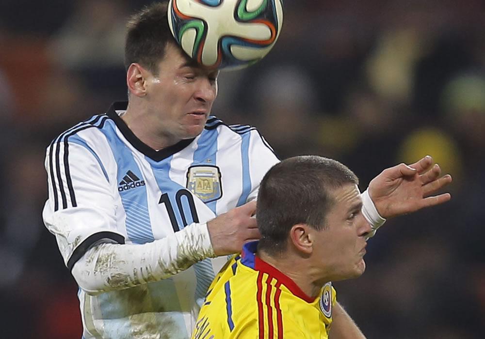 Lionel Messi (i) de Argentina en acción ante Razvan Rat (d) de Rumania durante un partido amistoso. Foto: EFE