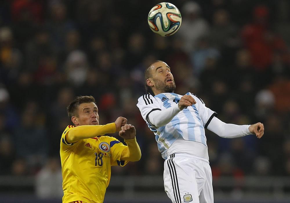 Rodrigo Palacio (d) de Argentina en acción ante Mihai Pintilii (i) de Rumania durante un partido amistoso. Foto: EFE