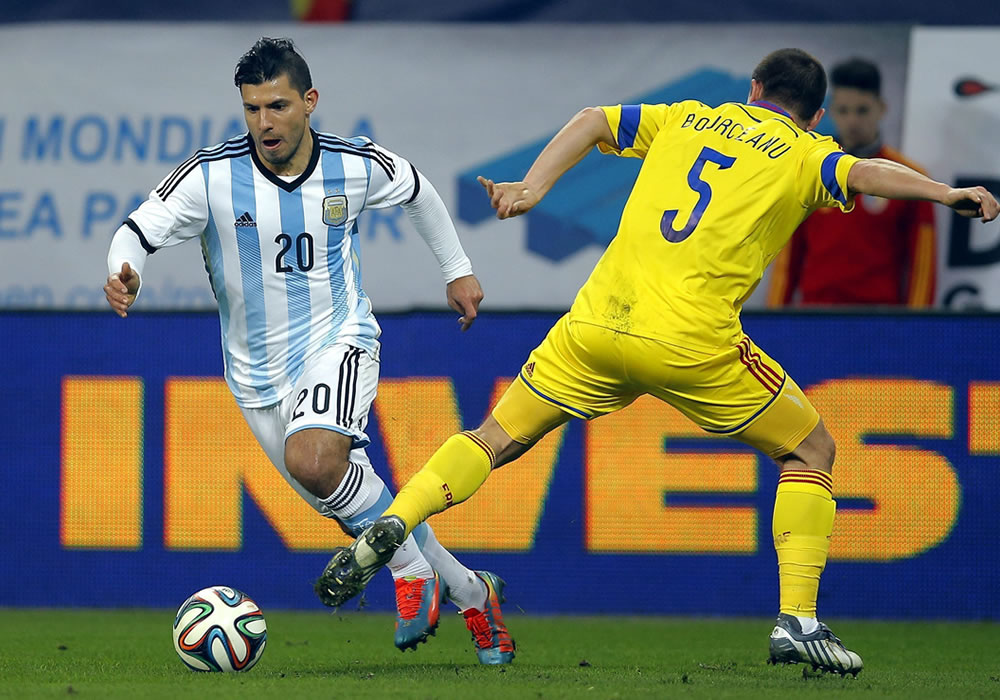 El delantero de la selección argentina, Sergio 'Kun' Agüero (i) lucha por el balón con Alexandru Bourceanu (d) de Rumanía. Foto: EFE