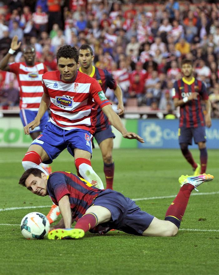 El delantero argentino del FC Barcelona Leo Messi (abajo) juega un balón desde el suelo ante el portugués Ilori, del Granada. Foto: EFE