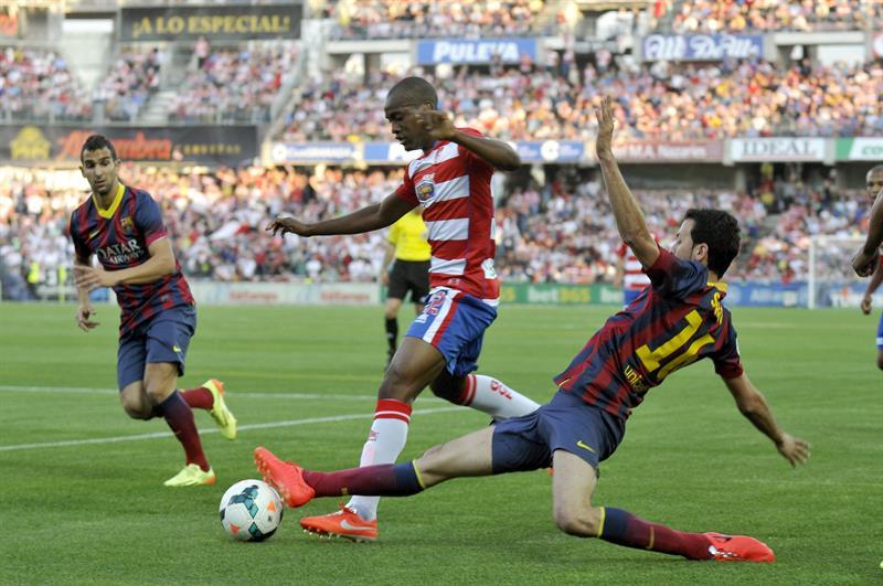El defensa francés del Granada Foulquier (c) trata de escapar de Sergio Busquets (d), del FC Barcelona. Foto: EFE