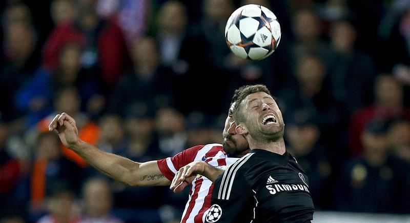 El delantero del Atlético de Madrid Raúl García (detrás) salta por un balón con Gary Cahill, del Chelsea. Foto: EFE