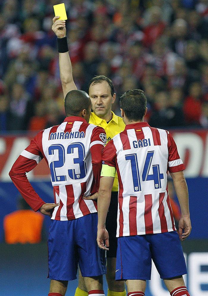 El árbitro sueco Jonas Eriksson (c) muestra la tarjeta amarilla al brasileño Miranda (i), del Atlético de Madrid. Foto: EFE