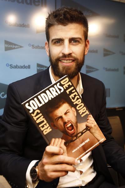 El defensa del FC Barcelona, Gerard Pique, posa con el libro de historias solidarias escrito por periodistas deportivos y prologado por él jugador barcelonista. Foto: EFE