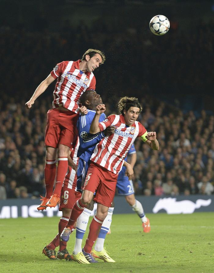 El delantero del Chelsea Demba Ba (c) lucha el balón con el uruguayo Diego Godín (i) y el portugués Tiago Mendes (d), del Atlético de Madrid. Foto: EFE