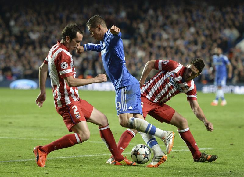 El delantero del Chelsea Fernando Torres (c) lucha el balón con Koke Resurreción (d) y el uruguayo Diego Godín (i), del Atlético de Madrid. Foto: EFE