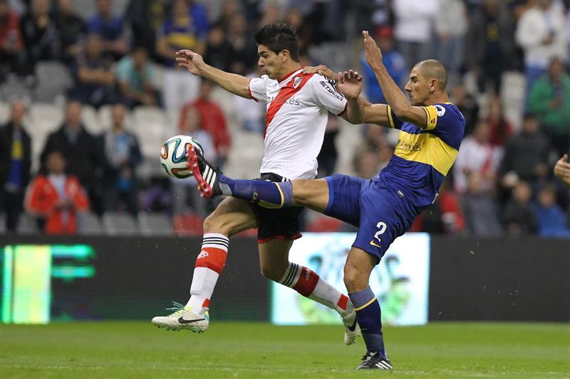 El jugador de River Plate Giovanni Simeone (i) es marcado por Daniel Díaz.. Foto: EFE