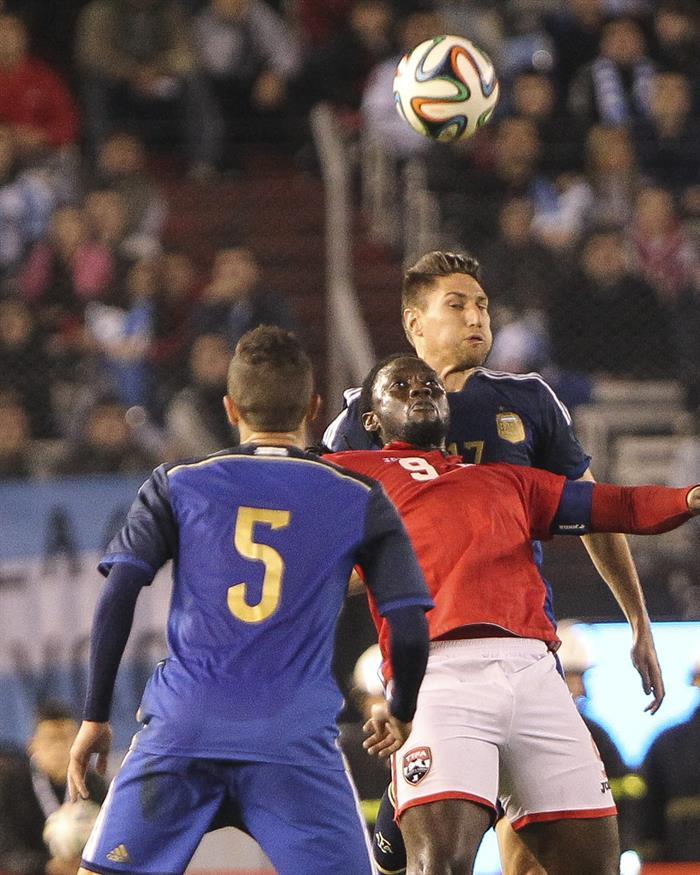 El jugador Federico Fernández (atrás) de Argentina disputa el balón con el jugador Kenwyne Jones (c) de la selección de Trinidad y Tobago. EFE