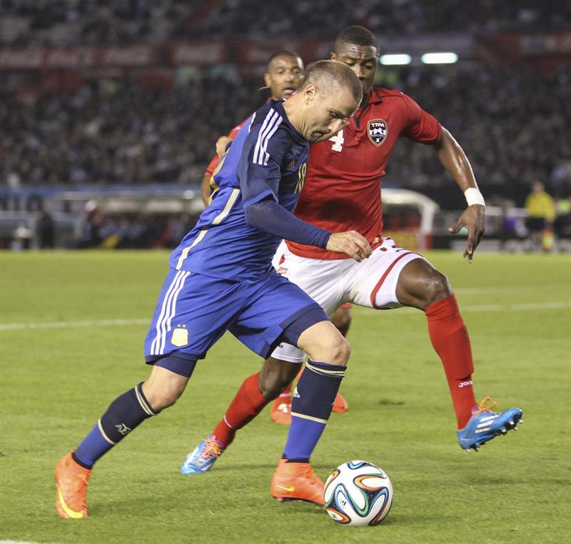 El jugador Rodrigo Palacio de Argentina disputa el balón con el jugador Justin Hoyte de la selección de Trinidad y Tobago. EFE
