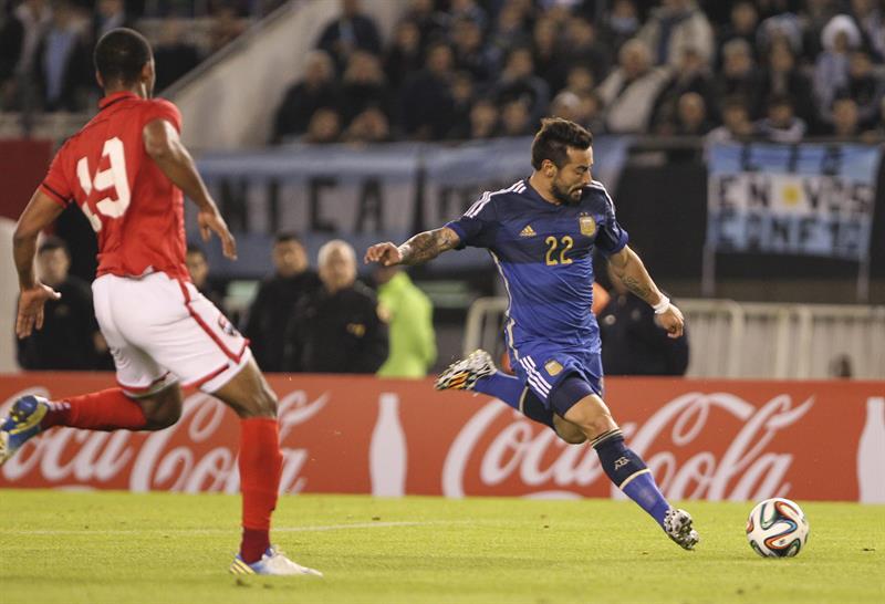 El jugador Ezequiel Lavezzi (d) de Argentina disputa el balón con el jugador Carlyle Mitchell de la selección de Trinidad y Tobago. EFE