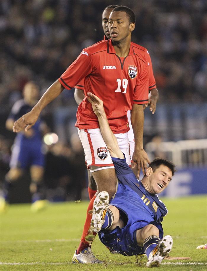 El jugador Lionel Messi (abajo) de Argentina cae ante Carlyle Mitchell (arriba) de la selección de Trinidad y Tobago. EFE
