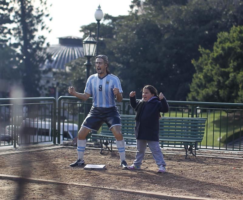 Una niña posa para una fotografía con la escultura del exjugador de la selección argentina Gabriel Batistuta. Foto: EFE