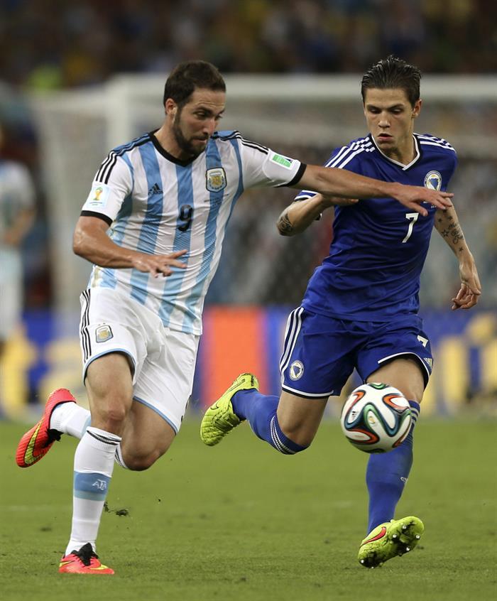 El delantero argentino Gonzalo Higuaín (i) lucha un balón con el centrocampista bosnio Muhamed Besic. Foto: EFE