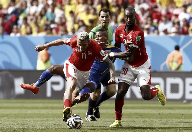 El centrocampista suizo Valon Behrami (i) controla el balón seguido por el centrocampista ecuatoriano Michael Arroyo (c) y el defensa suizo Johan Djourou. Foto: EFE