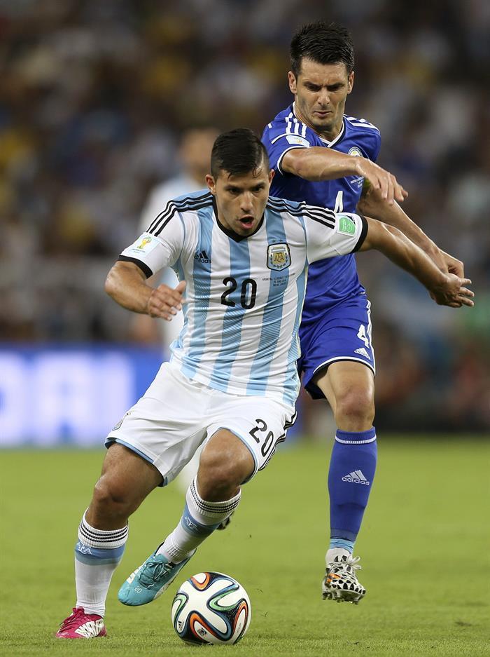 El delantero argentino Sergio 'Kun' Agüero controla el balón seguido por el defensa bosnio Emir Spahic,. Foto: EFE