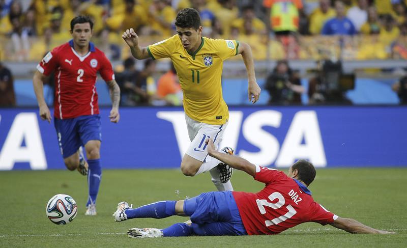 El centrocampista brasileño Oscar controla el balón ante el centrocampista chileno Marcelo Diaz (suelo). Foto: EFE