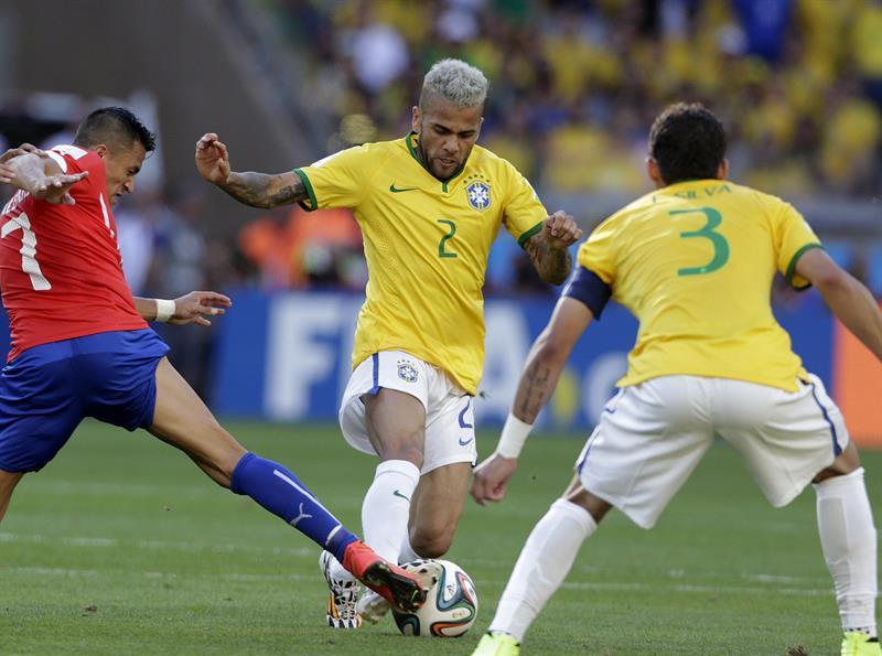 El defensa brasileño Dani Alves controla el balón ante el delantero chileno Alexis Sánchez (i). Foto: EFE