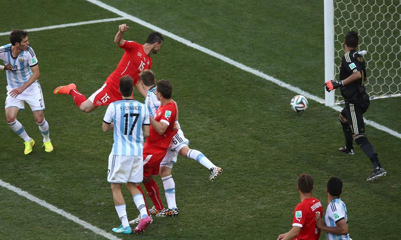 El balón lanzado por el centrocampista suizo Blerim Dzemaili (c-fondo) golpea el poste, durante el partido. EFE