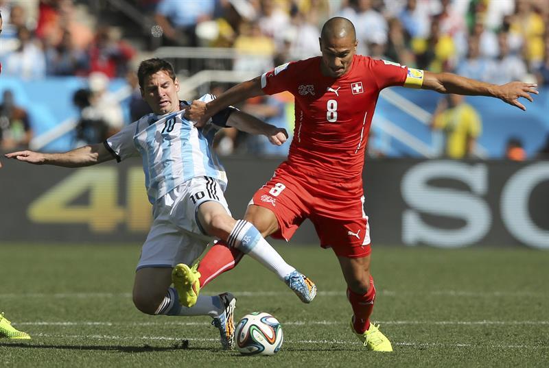 El delantero argentino Lionel Messi (i) lucha un balón con el centrocampista suizo Gokhan Inler (d). EFE