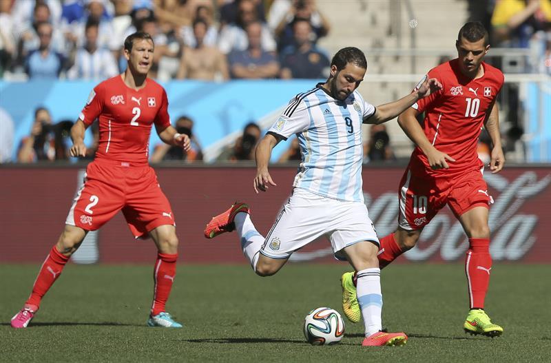 El delantero argentino Gonzalo Higuaín (c) con el balón ante los suizos Stephan Lichtsteiner (i) y Granit Xhaka (d). EFE