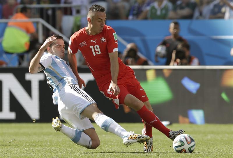 El delantero suizo Josip Drmic (d) lucha un balón con el centrocampista argentino Fernando Gago. EFE