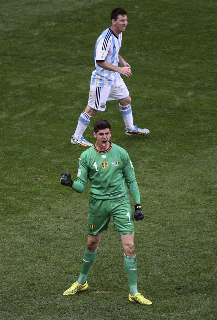 El portero belga Thibaut Courtois (en primer término) celebra haber parado un disparo del delantero argentino Lionel Messi (detrás). EFE
