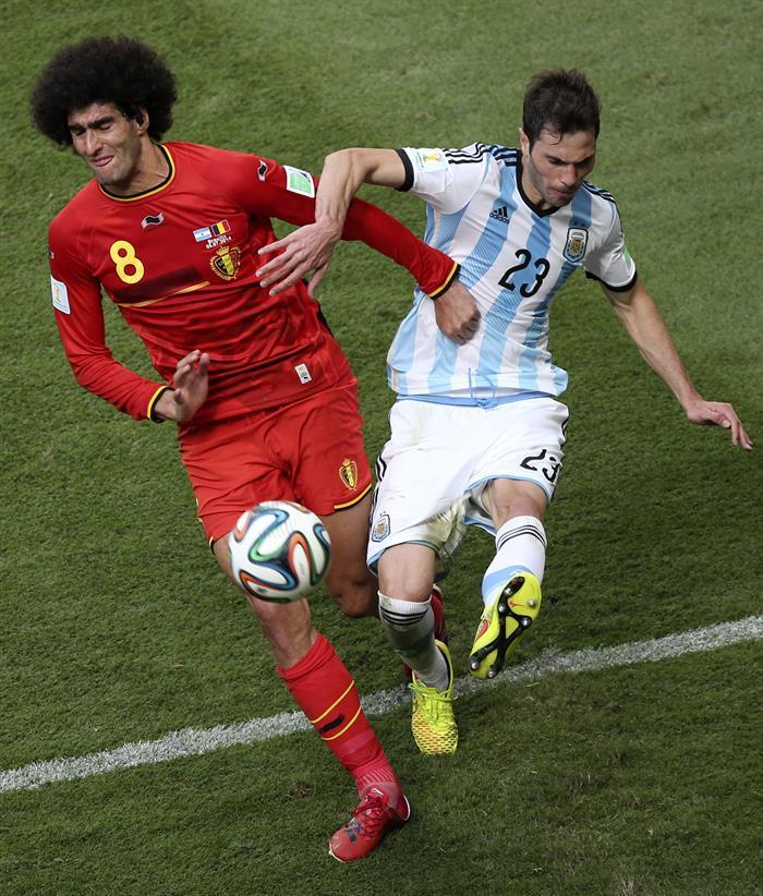 El defensa argentino Jose Maria Basanta (d) despeja ante el centrocampista belga Marouane Fellaini (i). EFE