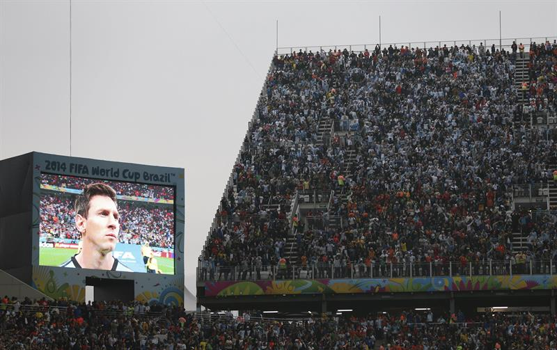 Miles de aficionados observan la imagen del delantero argentino Lionel Messi en una gran pantalla antes del inicio del partido. EFE