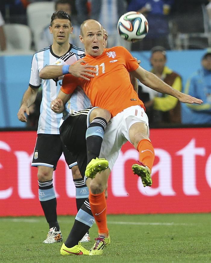 El delantero holandés Arjen Robben controla ante el centrocampista argentino Martín Demichelis (detrás). EFE