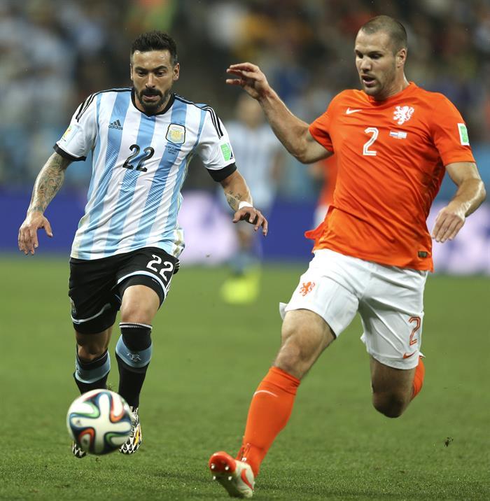 El delantero argentino Ezequiel Lavezzi (i) lucha un balón con el defensa holandés Ron Vlaar (d). EFE