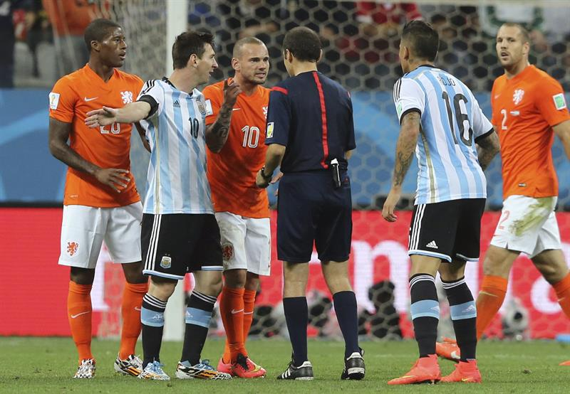 El delantero argentino Lionel Messi y el centrocampista holandés Wesley Sneijder conversan con el árbitro turco Cüneyt Cakir. EFE