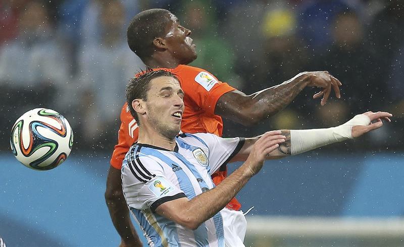 El centrocampista argentino Lucas Biglia (c) lucha un balón ante el centrocampista holandés Georginio Wijnaldum (detrás). EFE
