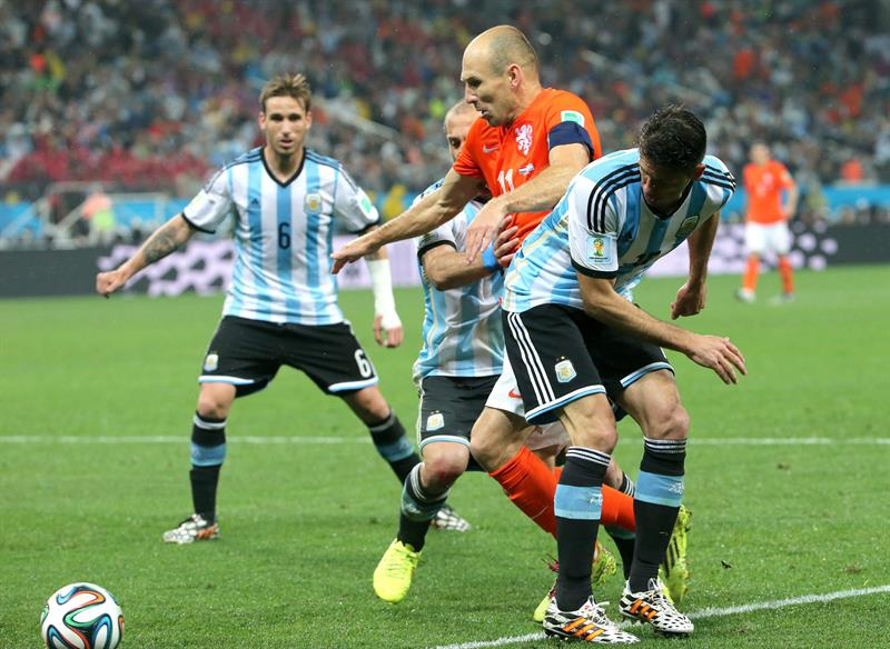 Arjen Robben of the Netherlands (C) in action against Argentina players during the FIFA World Cup 2014. EFE