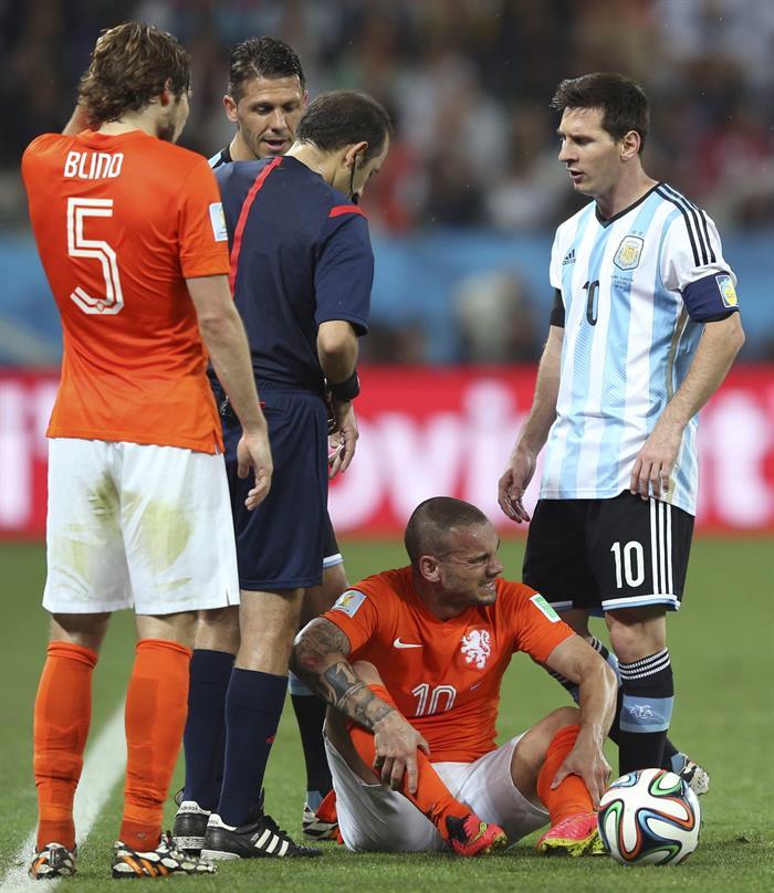 El centrocampista holandés Wesley Sneijder (2d) tendido sobre el terreno de juego ante el delantero argentino Lionel Messi. EFE