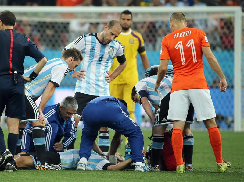Javier Mascherano of Argentina (on the pitch) gets assistant after a collision with a Dutch player during the FIFA. EFE