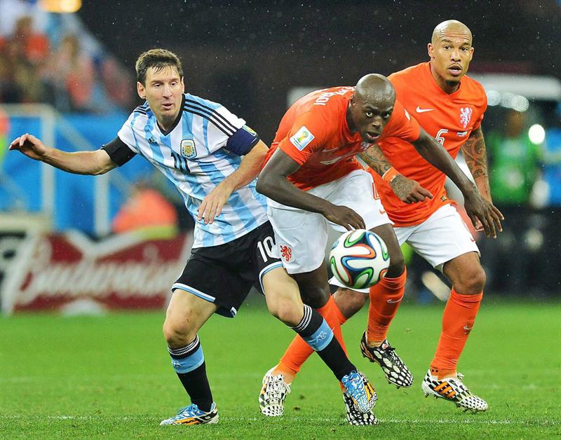 Dutch national soccer team players Bruno Martins Indi (C) and Nigel de Jong (R) in action with Argentinian national soccer team player Lionel Messi. EFE