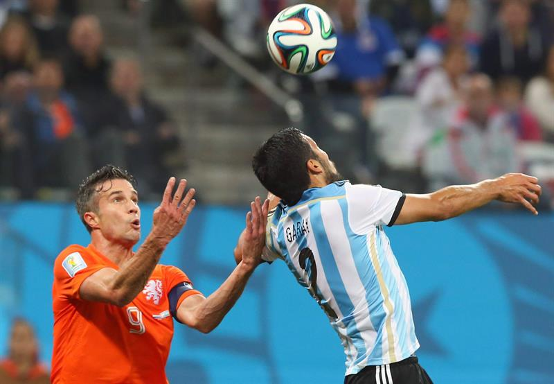 Robin van Persie of the Netherlands (L) and Argentina's Ezeuiel Garay (R) vie for the ball during the FIFA World Cup 2014. EFE