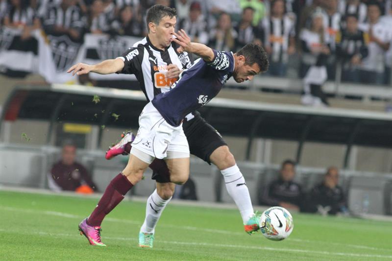 El jugador de Atlético Mineiro Leandro Donizete (atrás) disputa el balón con Lautaro Costa (adelante), de Lanús. EFE