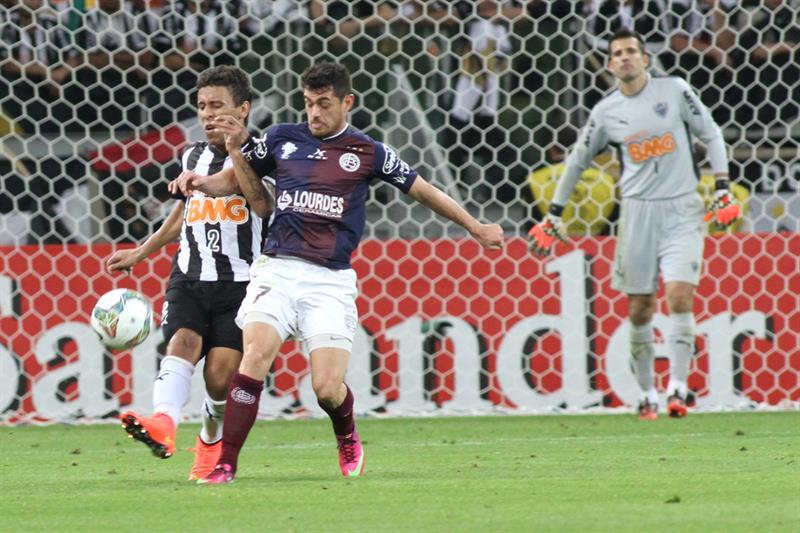 El jugador de Lanús Lautaro Acosta (c) disputa el balón con Marcos Rocha (i), de Atlético Mineiro. EFE
