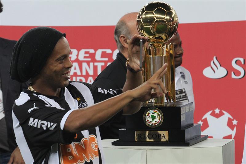 El jugador de Atlético Mineiro Ronaldinho Gaúcho celebra junto al trofeo de la Recopa Sudamericana. EFE