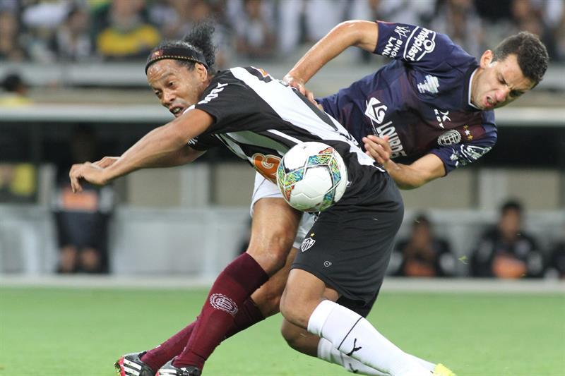El jugador de Lanús Jorge Ortiz (d) disputa el balón con Ronaldinho Gaúcho (i), de Atlético Mineiro. EFE