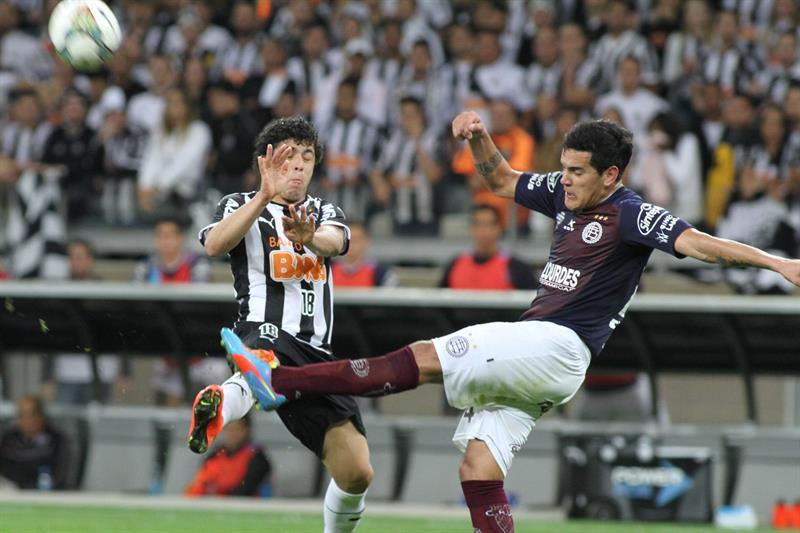 El jugador de Atlético Mineiro Luan (i) disputa el balón con Diego Braghieri (d), de Lanús. EFE